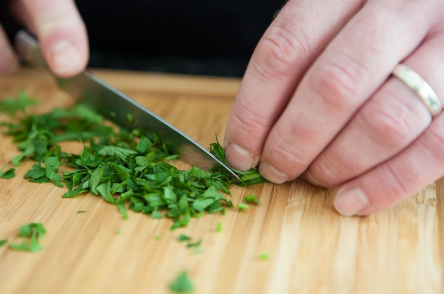 a chef finely chopping herbs on a cutting board